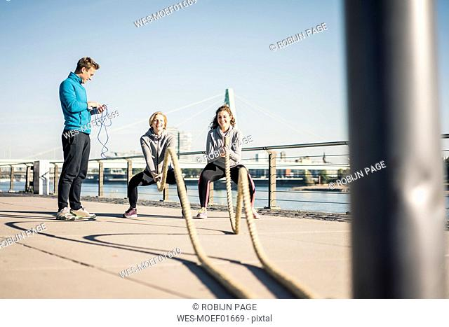 Friends training at the riverside, pulling rope
