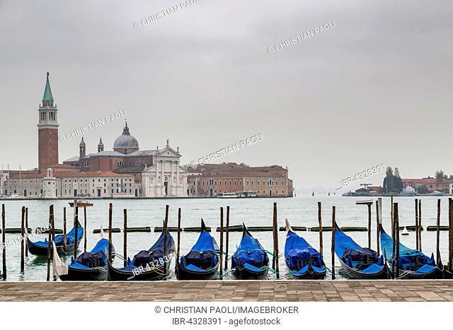 View of the Isola di San Giorgio Maggiore, in the foreground blue gondolas, Venice, Italy