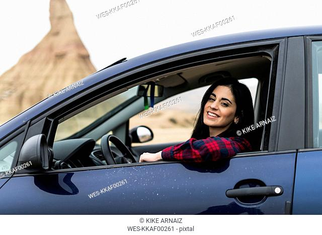 Spain, Navarra, Bardenas Reales, happy young woman looking out of car window
