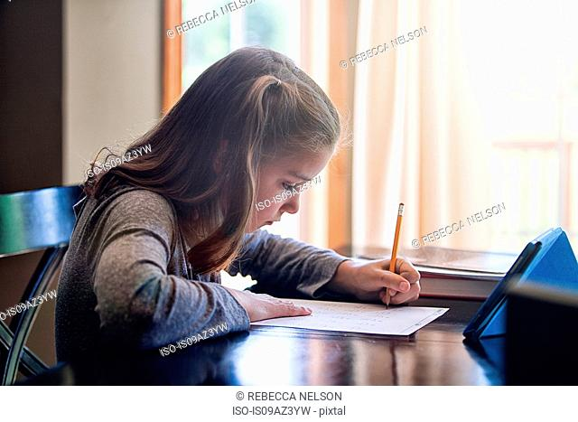 Side view of girl at desk writing