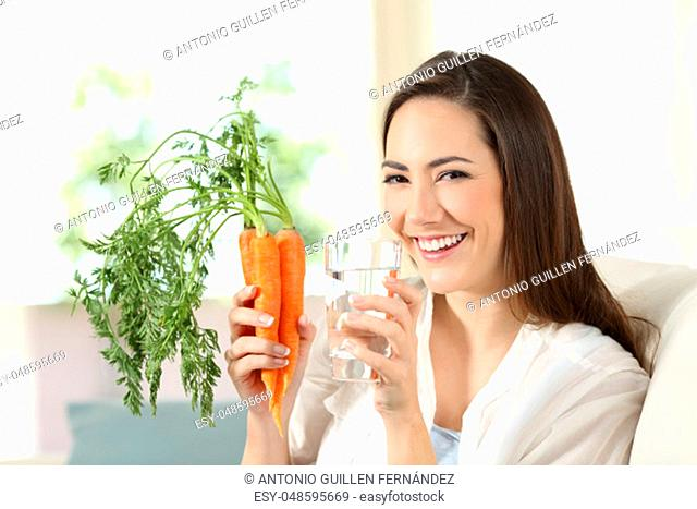Happy woman holding carrots and a water glass looking at camera sitting on a couch in the living room at home