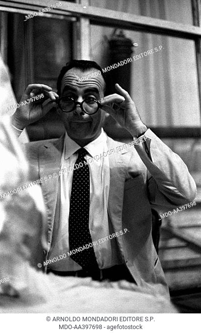 Vittorio Caprioli putting on a pair of glasses. Italian actor, director and screenwriter Vittorio Caprioli looking at himself in the mirror and putting on a...