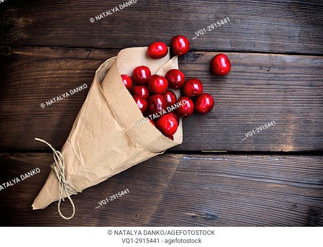 Ripe red cherry in a paper bag on a brown wooden background, empty space on the right