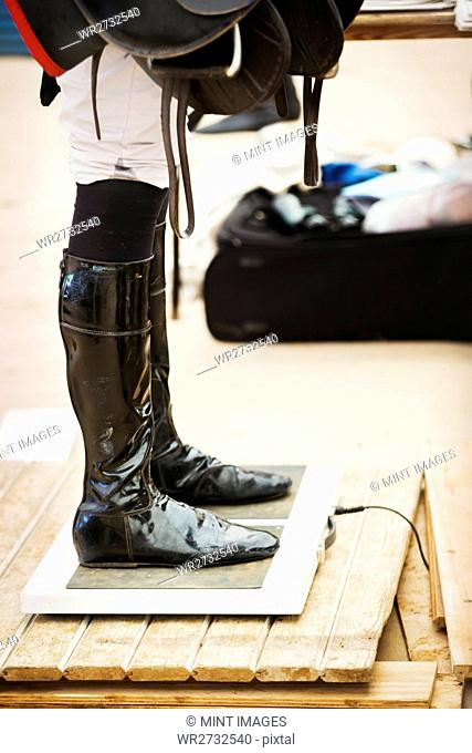 Rider wearing shiny black riding boots at the weigh in on weighing scale, holding a saddle, before or after a race
