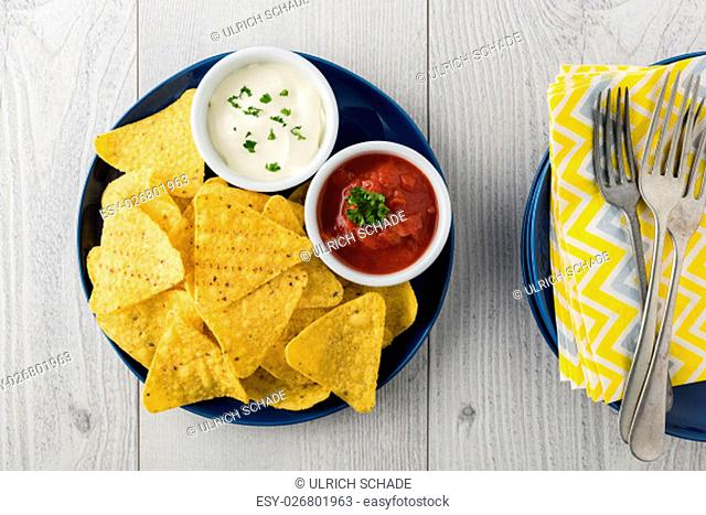 Nachos with salsa and sour cream dips