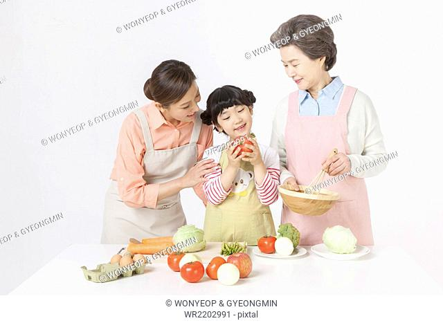 Mother, daughter, and grandmother in apron cooking together