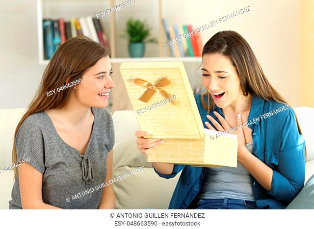 Two happy friends opening a gift box sitting on a couch in the living room at home