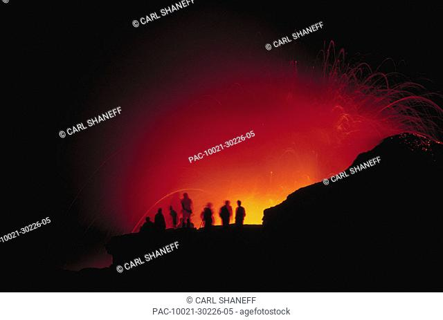 Hawaii, Big Island, Visitors view a glowing explosion of lava at night