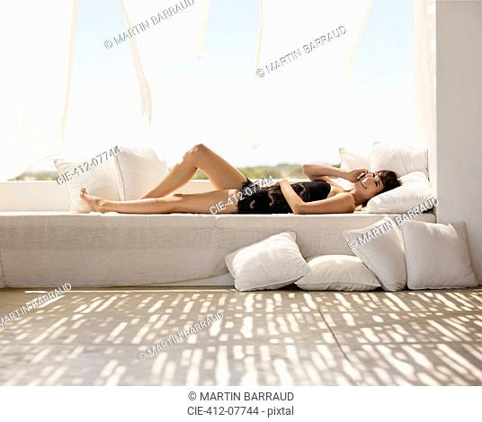 Smiling woman laying on patio sofa talking on cell phone