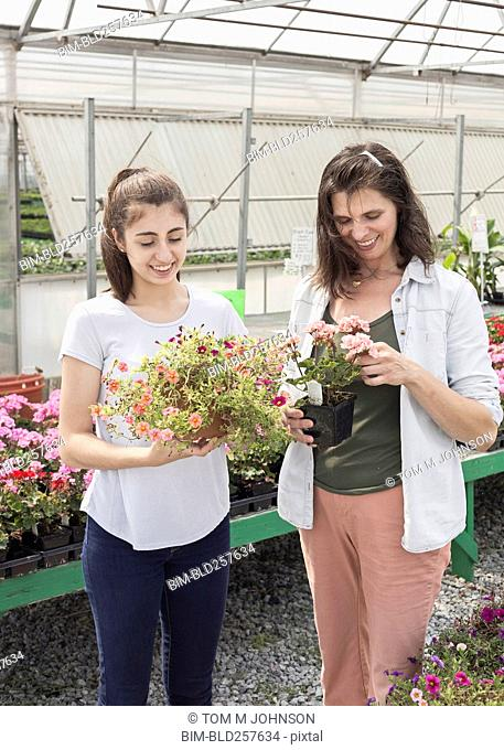 Caucasian mother and daughter shopping for flowers