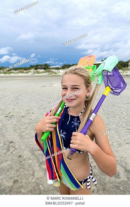 Caucasian girl on beach carrying net and shovels
