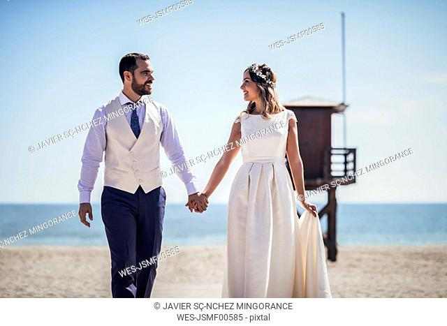 Happy bridal couple walking hand in hand on the beach