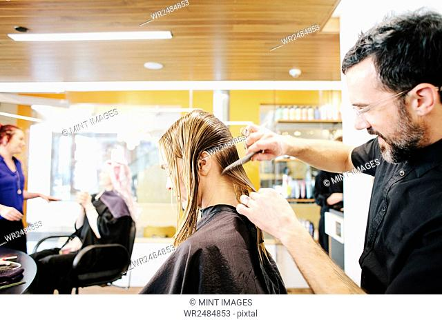 A hair stylist with a client, combing her long hair in sections