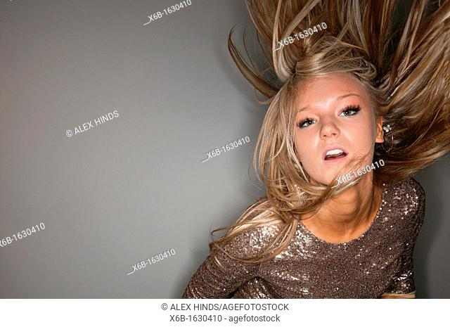 Portrait of young woman, 18-25 years, dancing and partying with hair flying in air