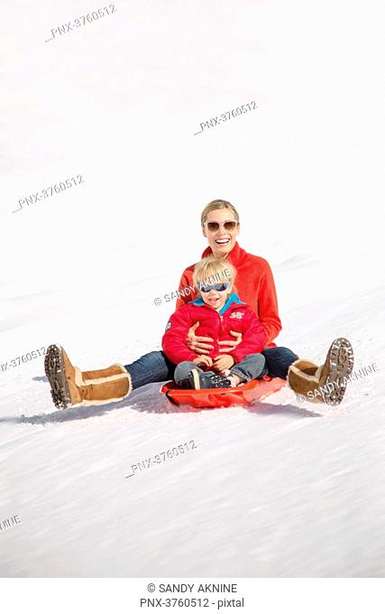 Portrait of smiling woman sitting with her childs on sled in snow, Crans-Montana, Swiss Alps, Switzerland