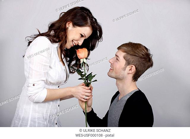 Man giving rose to woman against gray background, smiling