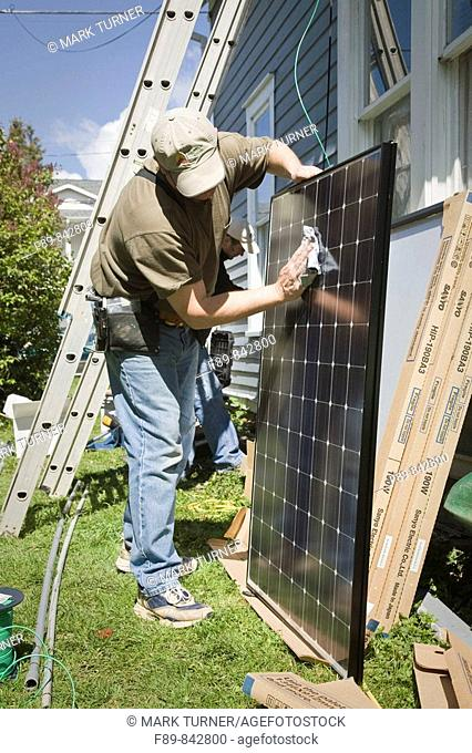 Man cleans surface of solar panel before installation
