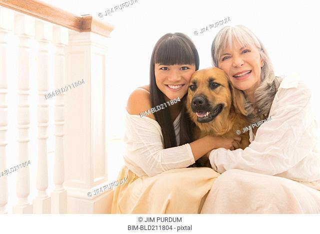Mother and daughter hugging dog on steps