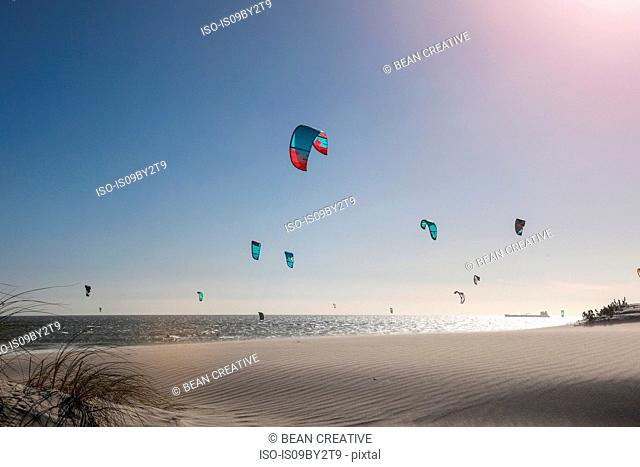 Group of kite surfers mid air over sea, Cape Town, Western Cape, South Africa