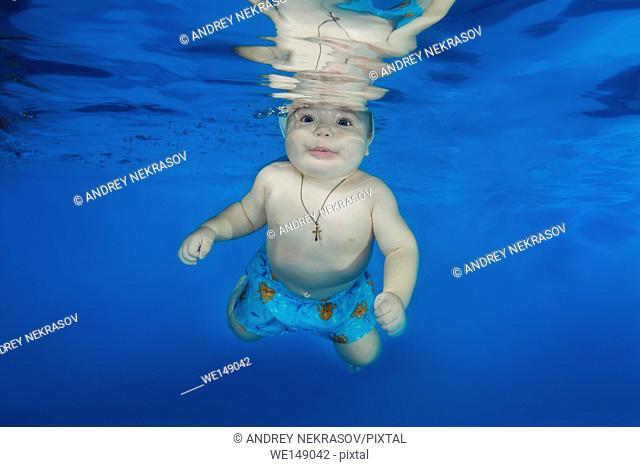 littlel boy in Santa's cap swimming underwater in the pool