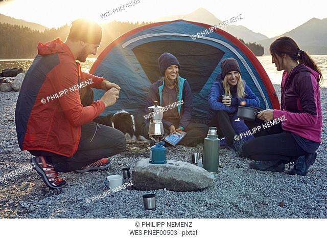 Group of hikers camping at lakeshore at sunset