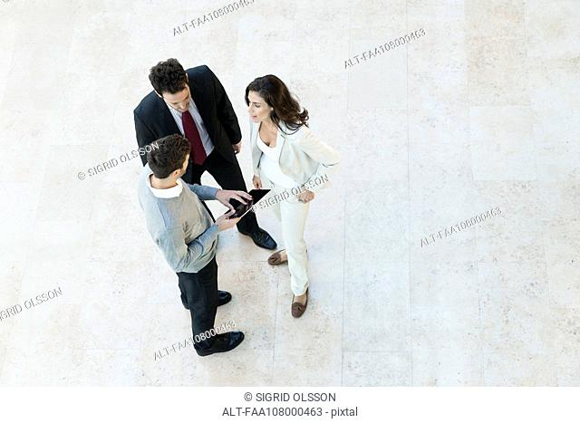 Businessman making proposal to associates using digital tablet