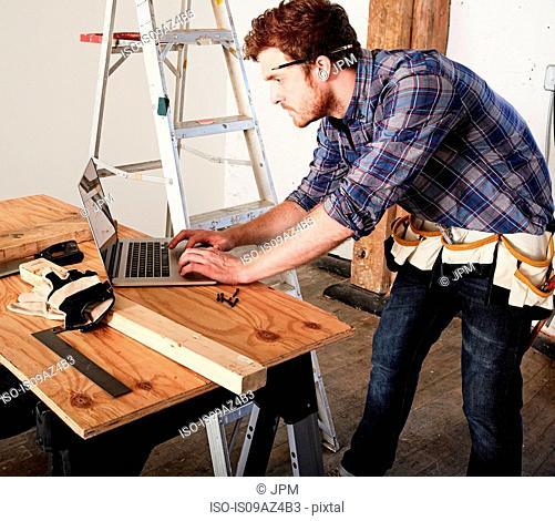 Carpenter in workshop using laptop