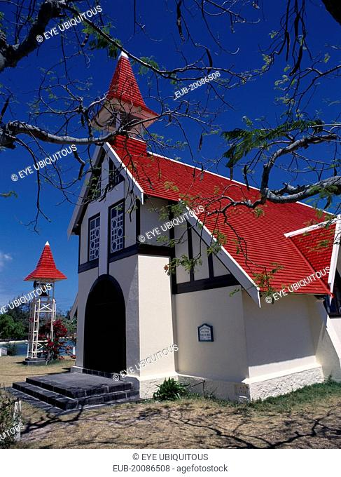 Marie-Reine Church. White painted exterior with red tiled roof and free standing bell tower, part framed by tree branches