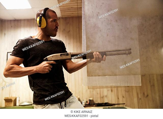 Man shooting with a rifle in an indoor shooting range