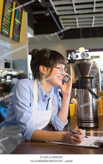 Close-up of a female store clerk talking on a cordless phone in a coffee shop