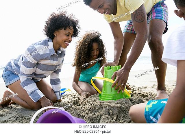 Family making sandcastle on beach