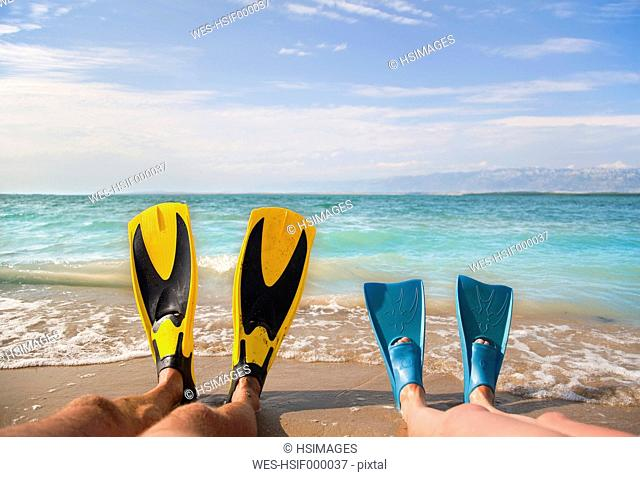 Croatia, Zadar, Couple with flippers relaxing on beach