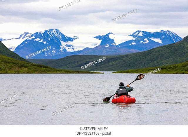 A man paddles a packraft across Landmark Gap Lake with the Alaska Range in the distance; Alaska, United States of America