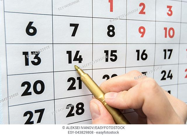 Hand marker indicates the date on the wall calendar