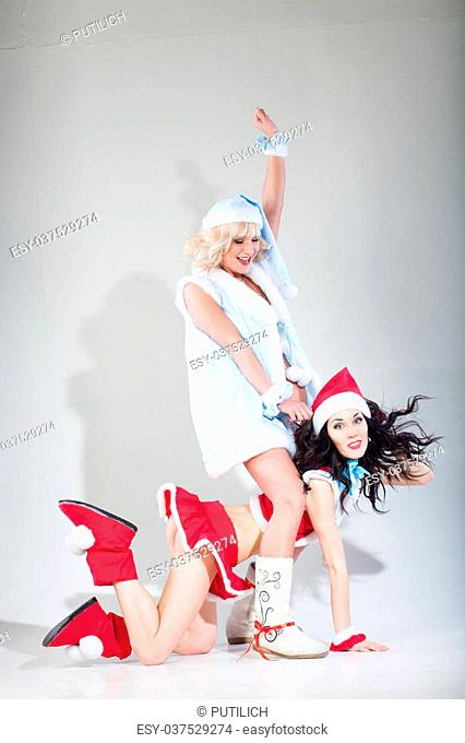 Two sexy young women in Christmas clothes posing over Christmas background