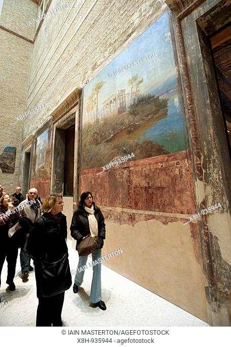 Visitors looking at old mural on wall in Egyptian courtyard gallery of newly renovated Neues Museum on the Museuminsel in central Berlin reopened after many...