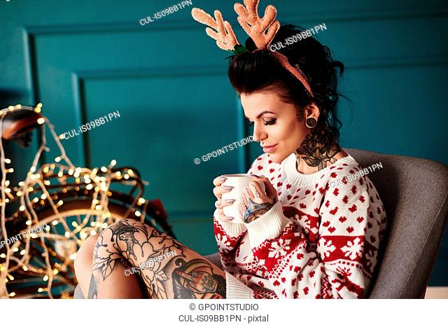 Young woman sitting at home, wearing christmas jumper and antlers, drinking hot drink