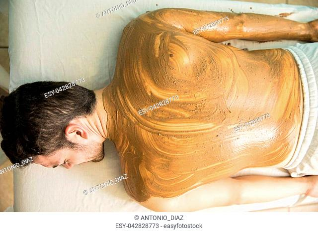 Top view of a young man falling asleep and enjoying a mud bath in a health spa