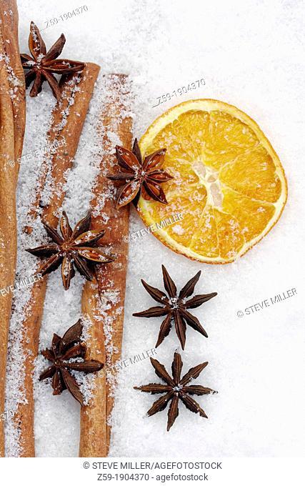 fruits of star anise - Illicium verum - cinnamon sticks - Cinnamomum cassia - dried orange slices - potpourri on artificial snowflakes