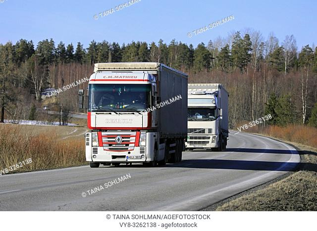 Salo, Finland - March 1, 2019: Two white semi trucks, Renault Magnum C. M. Mathieu in the front, transport goods on Finnish highway in early spring
