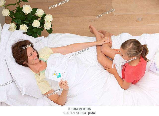 Mother laying in bed with holding get well card