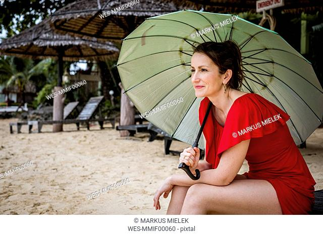 Thailand, Koh Phangan, portrait of smiling woman sitting on the beach with umbrella