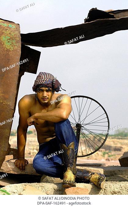 Man sitting under tin shade in jeans and turban ; Jodhpur ; Rajasthan ; India MR746A