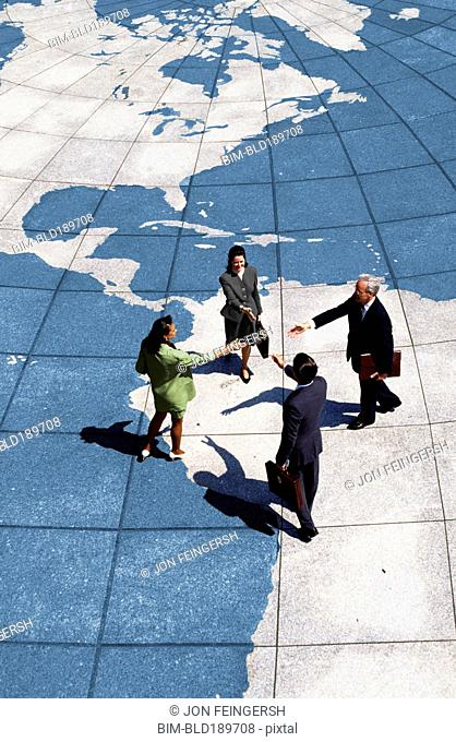Businesspeople shaking hands on map of globe