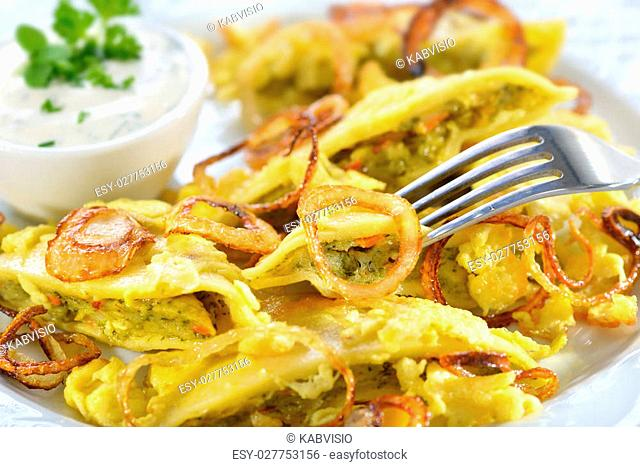 Fried Swabian ravioli (so-called'Maultaschen') with vegetarian filling served with roasted onions, scrambled egg and creamy herb cheese