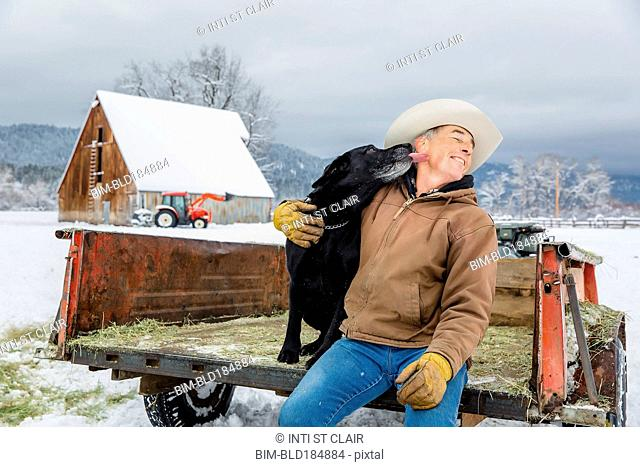 Dog licking face of Caucasian farmer in snowy truck