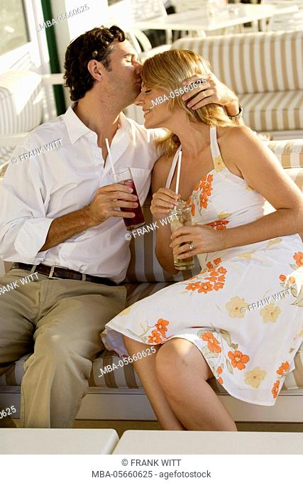 Couple in casual clothes is sitting with drinks on cafe terrace, he is kissing her forehead