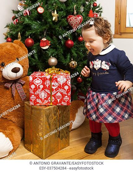 Beautiful toddler baby girl with surprised expression looking at gifts near the christmas tree