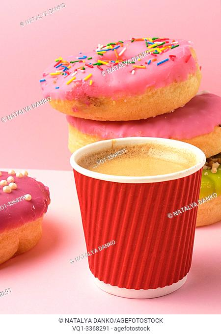round red glazed donut and paper cup with coffee on a pink background, close up