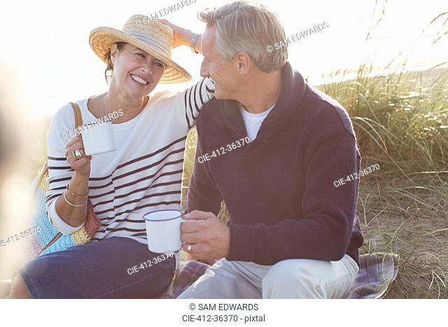 Mature couple drinking coffee in sunny beach grass